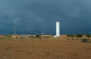 Sunlit tower against storm clouds