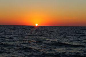 Sol sentado sobre el mar.
