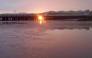 Golden sun caught between pier posts