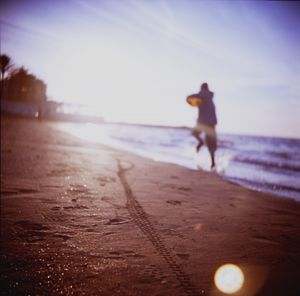 Boy running on beach square Lubitel