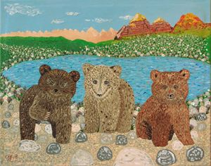 Three bear cubs by the lake
