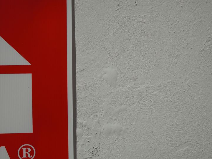 Red sign on white wall - Simon Goodwin